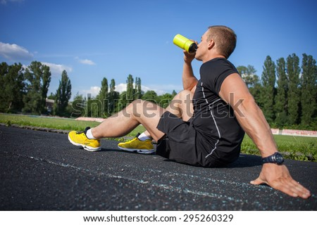 Handsome sportsman is drinking water from bottle with enjoyment. He is sitting on road in stadium and relaxing. He closed his eyes with satisfaction - stock photo