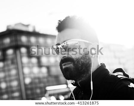 Handsome sportsman portrait in the city wearing sunglasses monochrome - stock photo