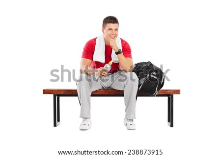 Handsome sportsman sitting on a wooden bench isolated on white background - stock photo
