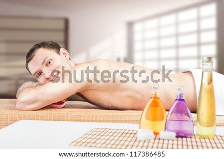 Handsome sporty man in spa salon. Young man is going to have massage in a spa center - stock photo