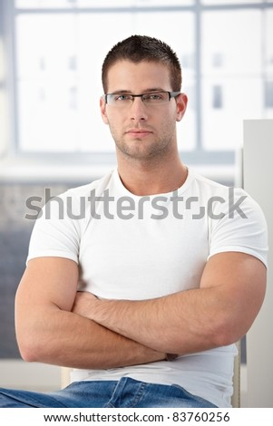 Handsome, sporty man sitting, wearing glasses.? - stock photo