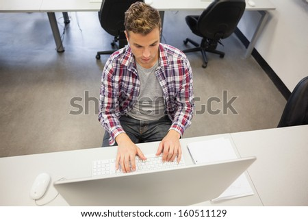 Handsome stern student working on computer in computer room at college - stock photo