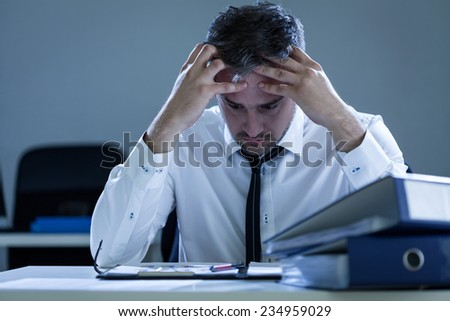 Handsome stressed businessman sitting at desk in his office - stock photo