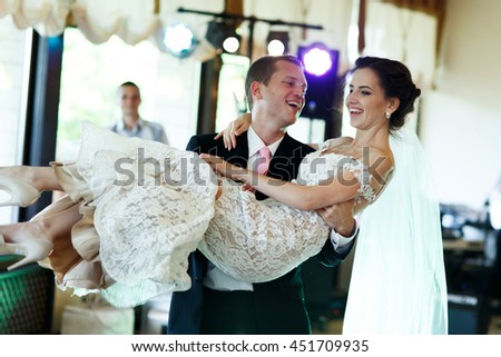 Handsome strong groom holding beautiful sexual brunette bride in arms - stock photo