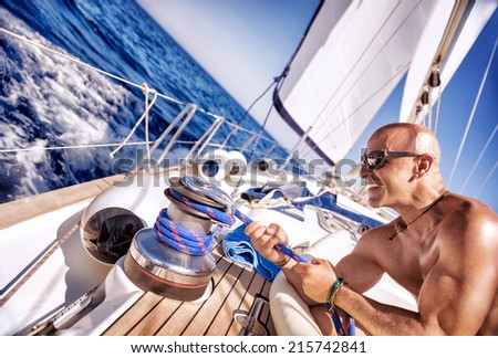 Handsome strong man working on sailboat, sailor enjoys crew duty, luxury holidays, yachting sport activities, sailing the oceans, summer vacation and recreation - stock photo