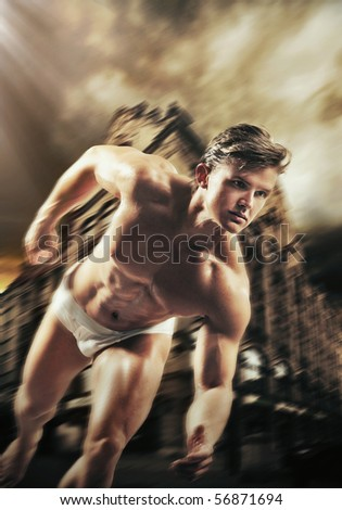 Handsome strongman running on a city street - stock photo