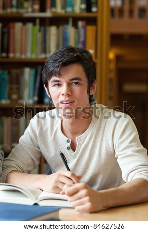 Handsome student reviewing his notes while looking at the camera