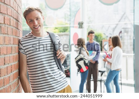 Handsome student smiling at camera at the university - stock photo