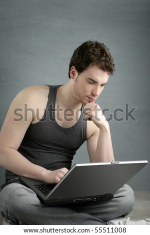 handsome student young man sit working on laptop over gray background - stock photo