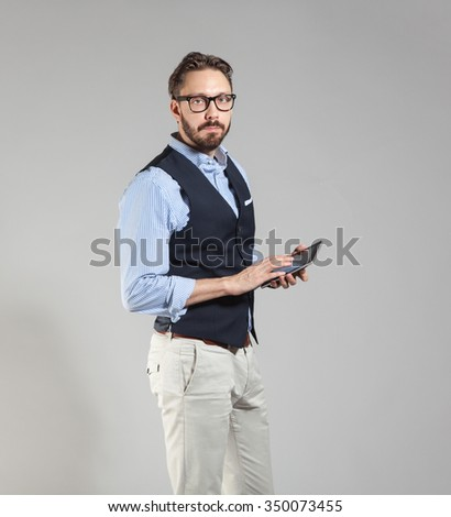 Handsome stylish bearded man in classic vest holding tablet in hands