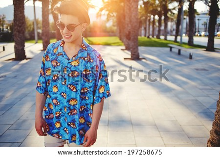 Handsome stylish man in bright summer clothes worth laughing at the magical summer sunset - stock photo