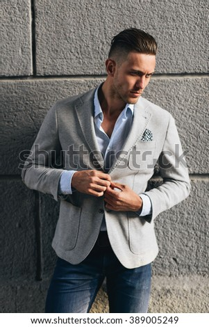 Handsome stylish man in grey suit posing opposite wall - stock photo