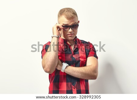 Handsome stylish man in hipster plaid shirt and sunglasses   - stock photo