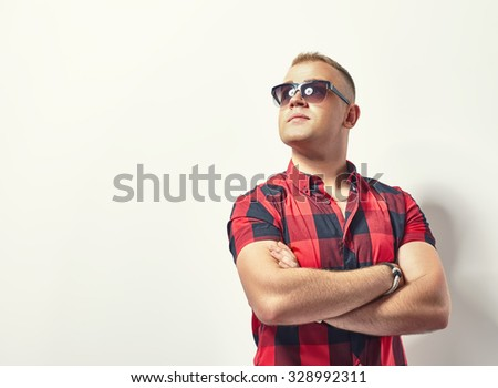 Handsome stylish man in hipster plaid shirt and sunglasses with copy space - stock photo