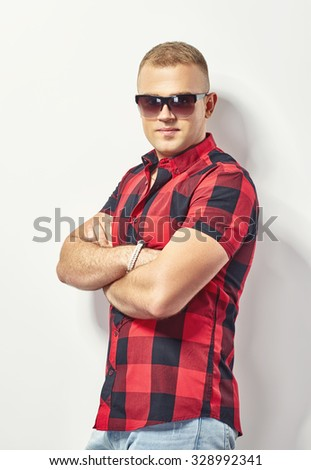 Handsome stylish man in sunglasses and hipster plaid shirt - stock photo