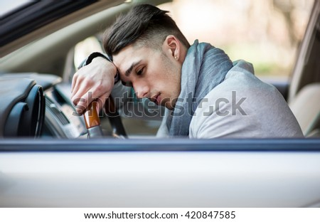 Handsome stylish man tired and sleepy in car feels dangerous
