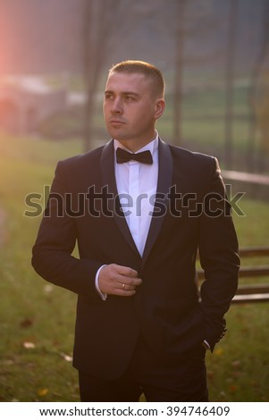 Handsome stylish young bridegroom in black wedding suit jacket white shirt on bow tie standing outdoor in forest on natural background, vertical picture - stock photo