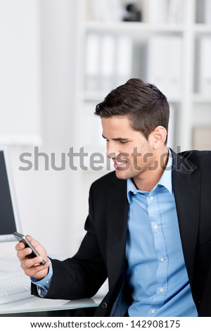 Handsome stylish young businessman smiling while looking at a message on the screen of his mobile phone while seated at his desk in the office
