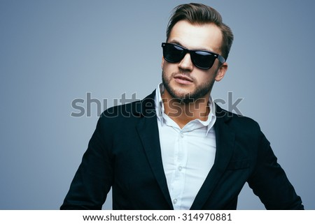 Handsome stylish young man. Brutal man with a beard and sunglasses - stock photo