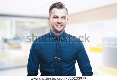 Handsome stylish young man in shirt looking at the camera. Office worker. Business decisions. Beautiful light background - stock photo
