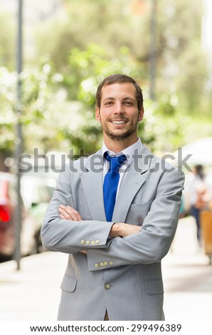 Handsome successful businessman professional in grey suit posing for camera at the park.