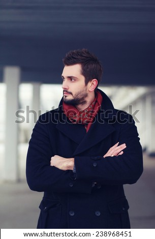 Handsome successful man stands hands crossed and confident looking away outdoors