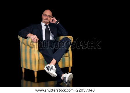 Handsome successful middle aged businessman with spectacles, studio shot, black background - stock photo