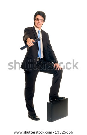 Handsome successful young businessman, laptop in hand, foot on briefcase, joyful expression, studio shot.