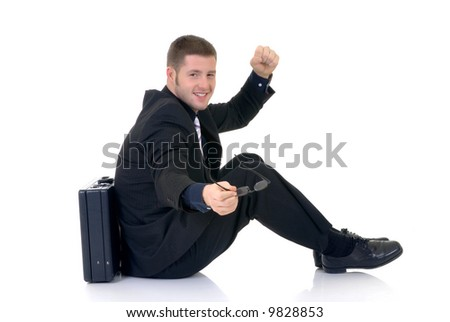 Handsome successful young businessman, sitting next to  briefcase, joyful expression, studio shot.