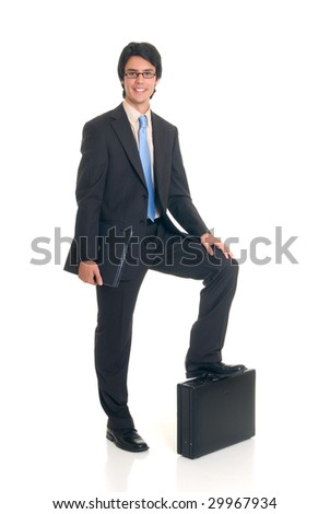 Handsome successful young businessman with briefcase and laptop, joyful expression, studio shot.