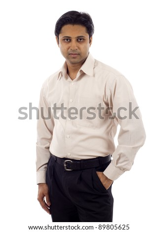 Handsome successful young Indian business with hand in pocket isolated over white background