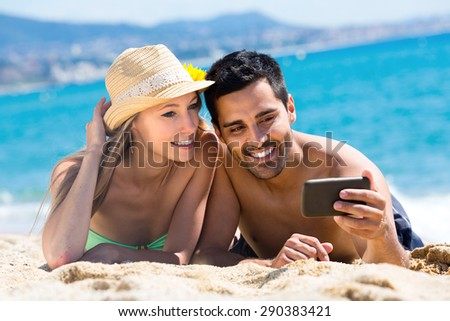 Handsome sun-tanned man is taking a self portrait of him lying on a beach with a sexual young woman