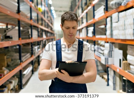 Handsome supervisor with clipboard at the warehouse. - stock photo