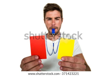 Handsome supporter showing red and yellow cards on white screen - stock photo