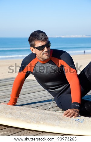 Handsome surfer wearing a wetsuit sitting next to his surf board. - stock photo