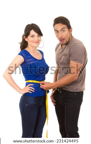 handsome surprised man holding measuring tape around thin fit young girl's waist concept of dieting fitness weightloss isolated on white - stock photo