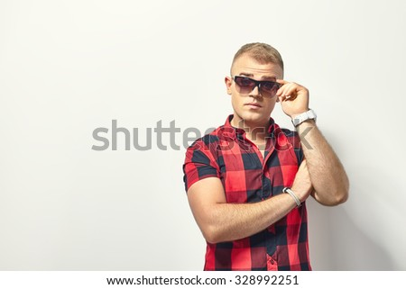Handsome surprised man in hipster plaid shirt and sunglasses  - stock photo