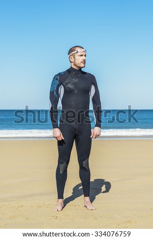 Handsome Swimmer ready to start swimming on the beach
