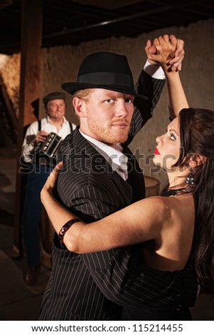 Handsome Tango dancer in pinstripe suit with sexy partner - stock photo