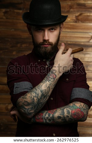 Handsome tattooed man with cigar posing over wood wall - stock photo