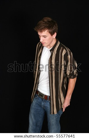 handsome teen boy in jeans looking down on black background