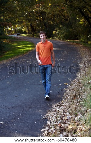 handsome teen boy walking on curving road in fall
