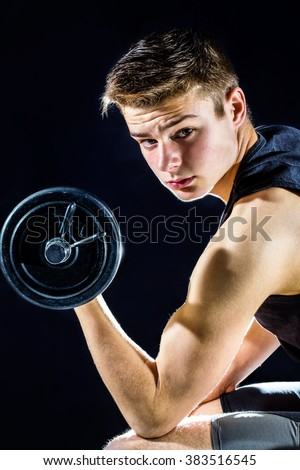 Handsome teen boy with working out with dumbbell. Isolated against black background.