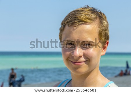 handsome teen has fun swimming in the ocean under blue sky - stock photo