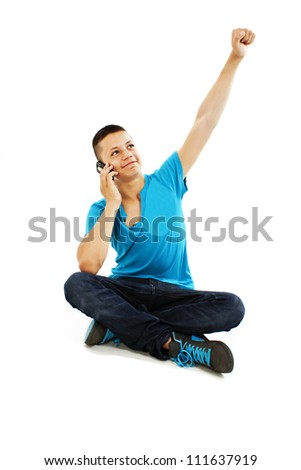 Handsome teenage boy cheering during phone call. Isolated on a white background