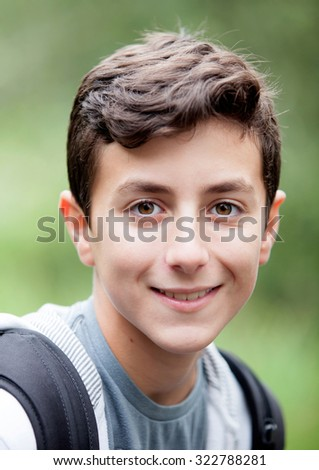 Handsome teenage boy looking at camera and smiling outdoors