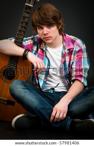 Handsome teenager boy holding his guitar over dark background - stock photo