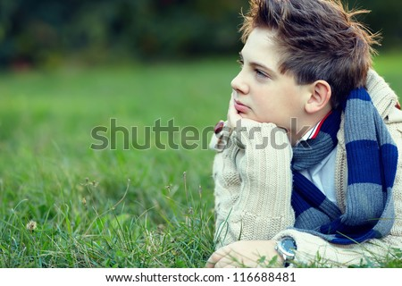 handsome teenager boy lies on grass and thinks - stock photo