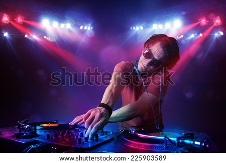 Handsome teenager dj mixing records in front of a crowd on stage - stock photo