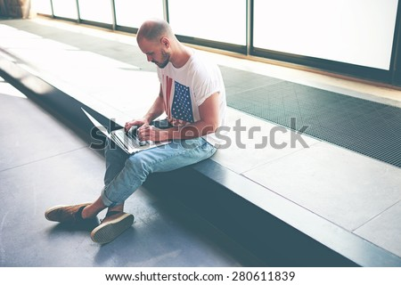 Handsome teenager studying on his laptop computer while sitting in university hall, male freelancer busy working on notebook while typing text on keyboard, young man making money on-line, e-business - stock photo